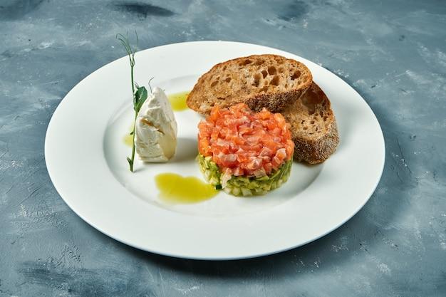Tartare de saumon et d'avocat, croûtons dans une assiette blanche sur une surface grise.