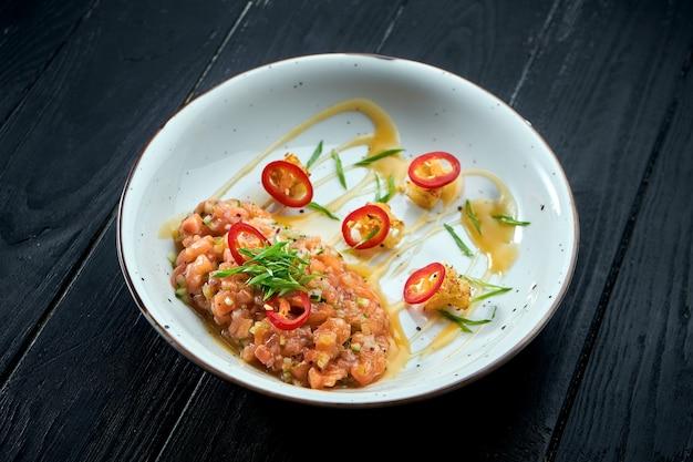 Tartare de saumon à l'avocat et piment fort sur une plaque blanche