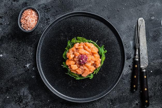 Tartare de saumon cru ou tartare aux oignons rouges, roquette et câpres en assiette noire. table noire. vue de dessus.