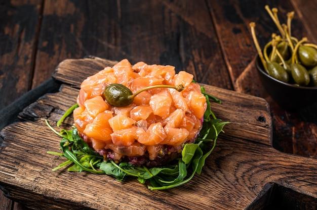 Tartare de saumon ou tartare aux oignons rouges, avocat, roquette et câpres. table en bois sombre. vue de dessus.