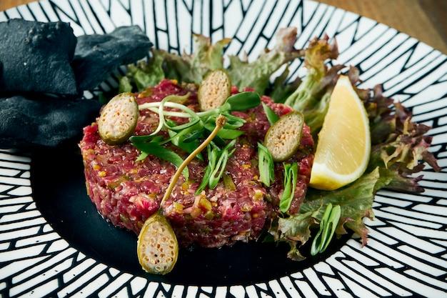 Tartare de steak de boeuf aux câpres sur une plaque en céramique inhabituelle. apéritif plat principal. fermer,