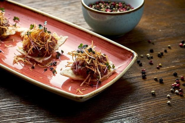 Tartare de steak de boeuf servi sur croûtons dans une assiette rouge sur fond de bois. nourriture de restaurant.