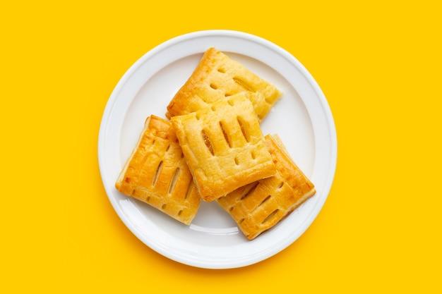 Tarte à l'ananas en plaque blanche sur fond jaune.