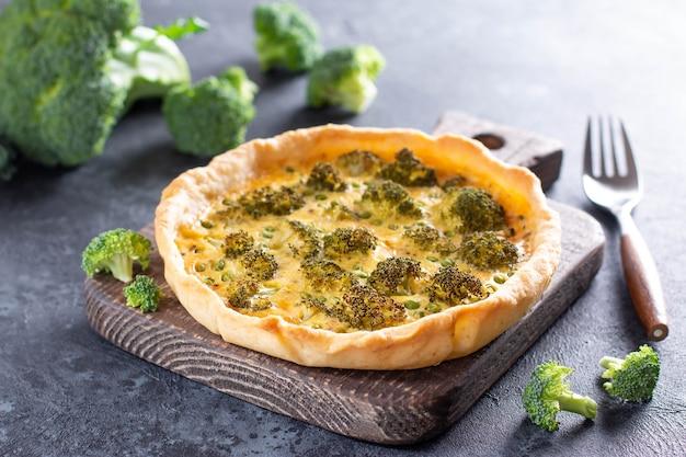 Tarte au brocoli et fromage sur une planche à pâtisserie en bois sur un fond de béton gris