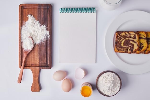 Tarte au cacao tranchée et servie dans une assiette en céramique blanche avec des ingrédients et un livre de recettes autour.