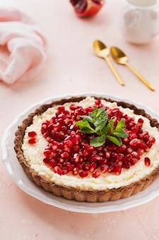 Tarte au chocolat dessert maison avec crème de coco et grenade et menthe sur un fond de table rose