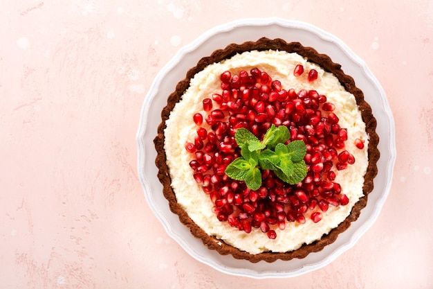 Tarte au chocolat dessert maison avec crème de noix de coco et grenade et menthe sur fond de table rose. vue de dessus