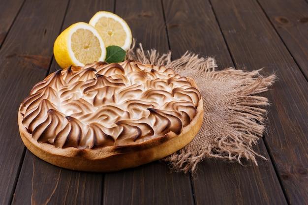 Tarte au citron de bon goût à la crème blanche servi sur une table en bois