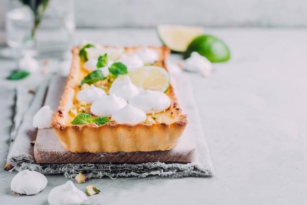 Tarte au citron vert et au citron, aux pistaches de noix et à la meringue. gateau aux agrumes
