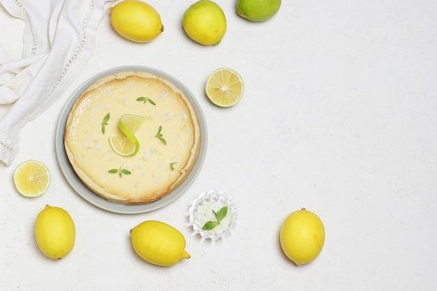 Tarte au citron vert sur bois blanc avec limes