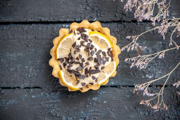 Tarte au citron vue de dessus avec branche de fleurs séchées au chocolat sur une surface en bois sombre