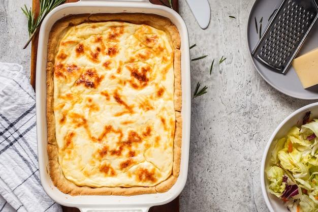 Tarte au fromage au romarin dans le plat à four, fond gris, vue de dessus.