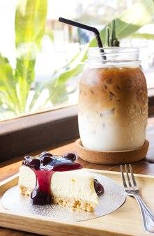 Tarte au fromage aux bleuets sur une assiette en bois servie avec du café tardif. vue du café.