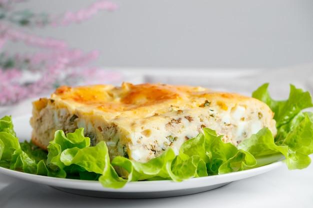 Tarte au poisson savoureuse sur une assiette. un morceau de gâteau avec du maquereau et des verts sur fond blanc.