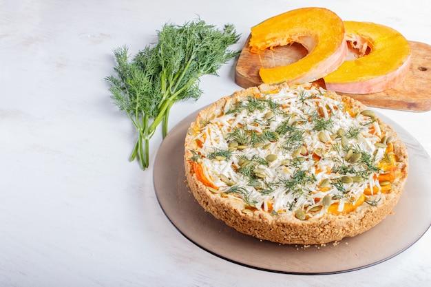 Tarte au potiron sucrée au fromage et à l'aneth sur bois blanc.