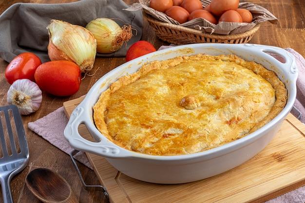 Tarte au poulet sur le plateau et légumes sur la table en bois