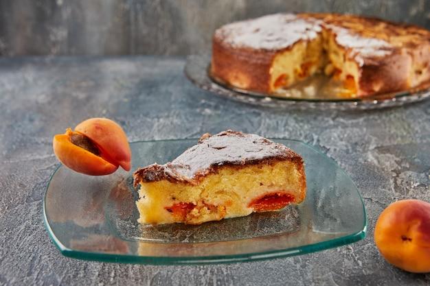 Tarte aux abricots et aux amandes avec morceau coupé sur plaque de verre sur fond de béton.