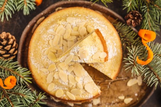 Tarte aux amandes de noël (norvégienne) traditionnelle dans des décorations de noël, fond sombre.