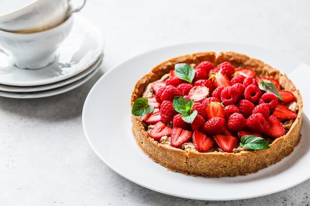 Tarte aux baies entières avec framboises, fraises et crème sur un plat blanc