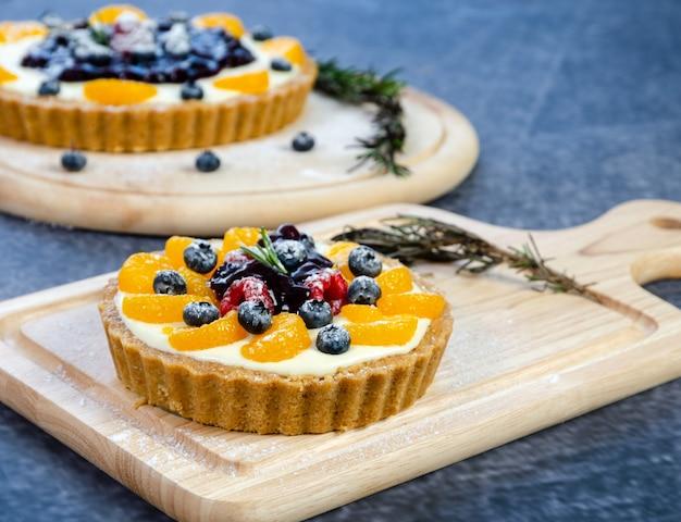 Tarte aux bleuets au fromage à la crème maison sans cuisson garnie d'une sauce aux bleuets, myrtilles fraîches, framboises et fruits orange servis sur une planche à découper en bois