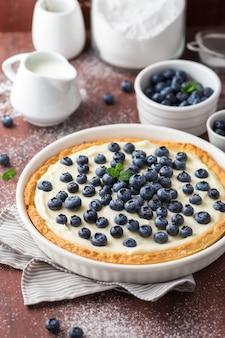 Tarte aux bleuets à la crème fouettée sur une table en bois