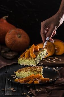 Tarte aux courgettes avec citrouille cuite au four sur une spatule dans les mains des femmes dans la cuisine, sur un fond de surface en bois sombre avec fond.