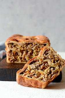 Tarte aux crêpes avec viande et champignons sur fond gris. gâteau aux crêpes sous forme de pain.