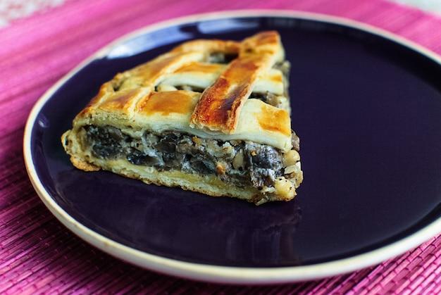 Tarte aux épinards et au fromage un morceau sur fond de tapis rose plaque bleue