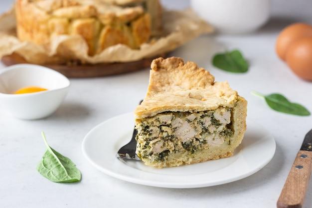 Tarte aux épinards, au poulet et à la ricotta avec des feuilles d'épinards fraîches, de la ricotta et des œufs.