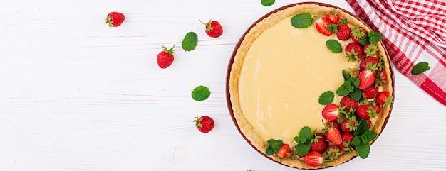 Tarte aux fraises et crème fouettée décorée de feuilles de menthe sur table lumineuse.