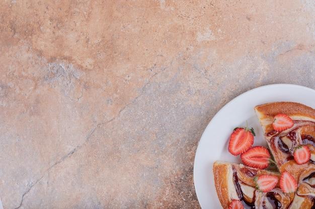 Tarte aux fraises dans une assiette blanche avec des fruits autour.