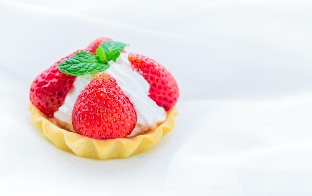 Tarte aux fraises avec feuille de menthe sur fromage à la crème sur fond de tissu blanc, gâteau minimal et boulangerie