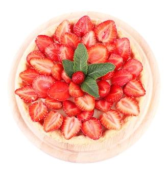 Tarte aux fraises avec des feuilles de menthe verte isolées sur une surface blanche