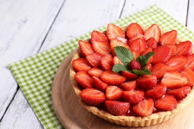 Tarte aux fraises sur plateau en bois, sur bois de couleur