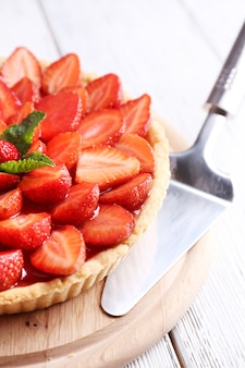 Tarte aux fraises sur plateau en bois, sur fond de bois de couleur
