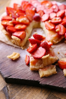 Tarte aux fraises sur plateau en bois, sur fond de bois rustique
