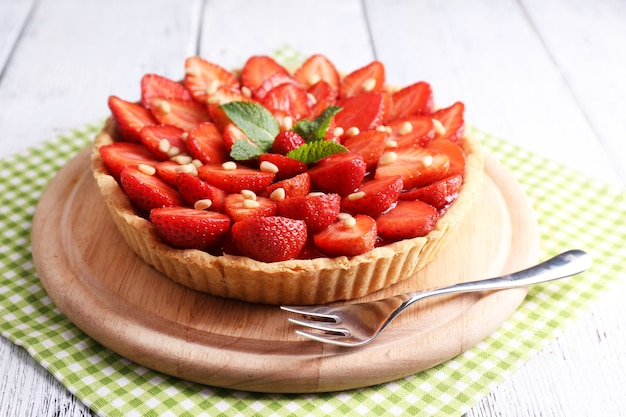 Tarte aux fraises sur plateau en bois, sur une surface en bois de couleur