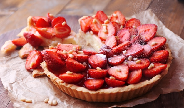 Tarte aux fraises sur plateau en bois, sur table en bois rustique