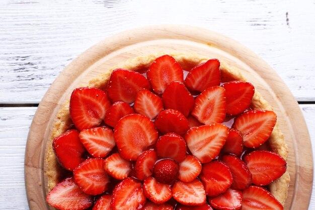 Tarte aux fraises sur une surface en bois de couleur