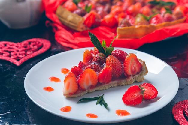 Tarte aux fraises sur table en bois noir plaque blanche.