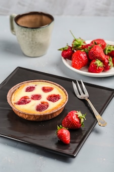 Tarte aux fraises avec une tasse de café sur un fond clair
