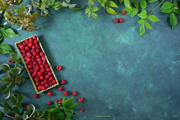 Tarte aux framboises sur fond vert avec des branches et des feuilles de framboise.