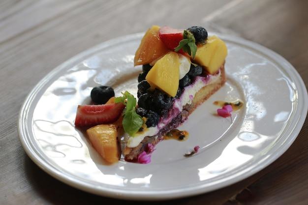 Tarte aux fruits frais en plaque blanche sur une table en bois