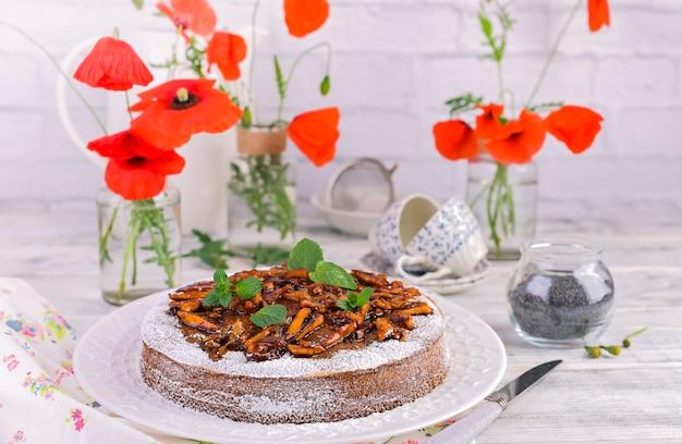 Tarte aux graines de pavot sur fond blanc. pâtisseries et fleurs rouges