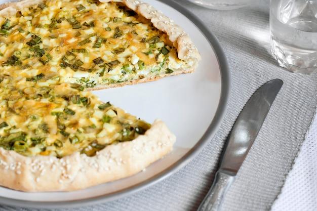 Tarte aux œufs et oignons verts sur une assiette