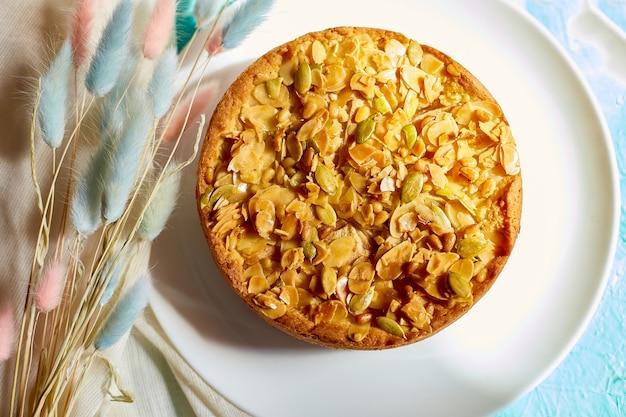 Tarte aux pommes ou aux poires, tarte aux noix caramel sur table bleue avec lumière du soleil