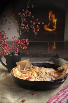 Une tarte aux pommes et un bouquet de fleurs sont sur la table