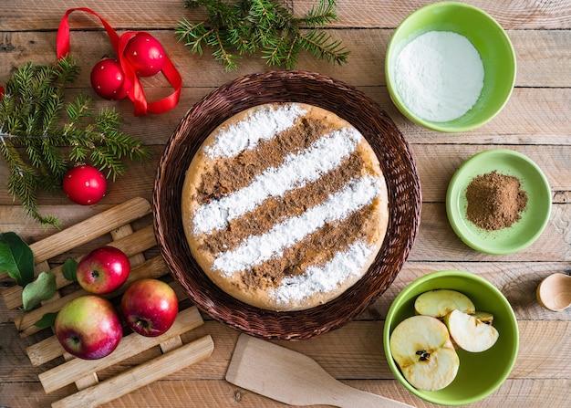 Tarte aux pommes à la cannelle maison ronde avec des décorations de noël et des ingrédients pour cuisiner autour