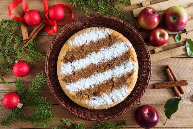 Tarte aux pommes à la cannelle maison ronde sur une table en bois avec des décorations de noël autour