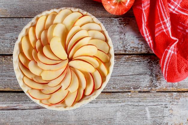 Tarte aux pommes crue sur une table en bois. prêt pour la cuisson